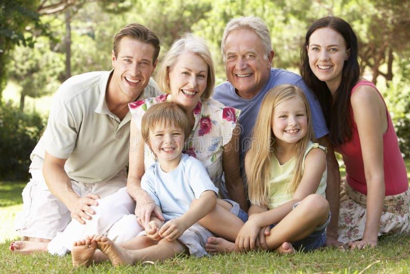 Trzy pokoleń Rodzinny obsiadanie W parku Wpólnie zdjęcie royalty free