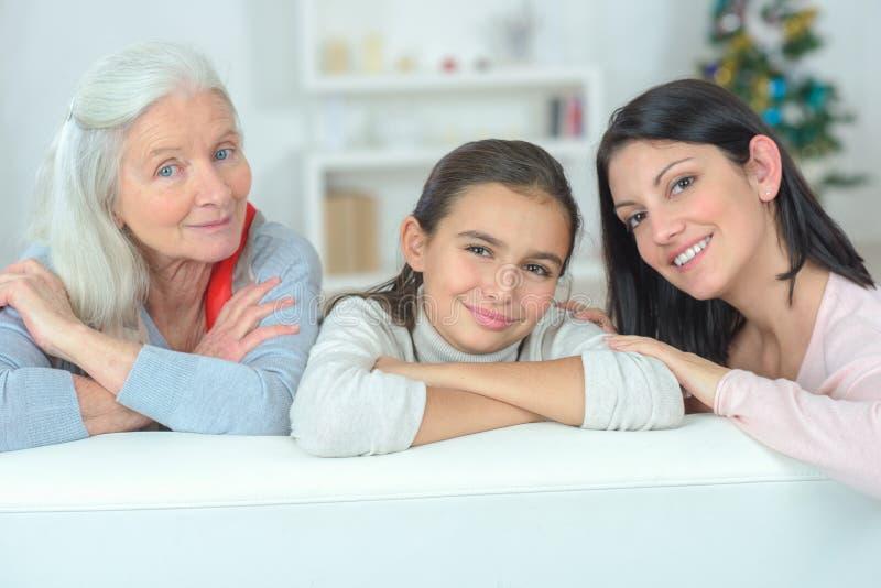 Trzy pokoleń rodzinny odpoczywać na leżance fotografia stock