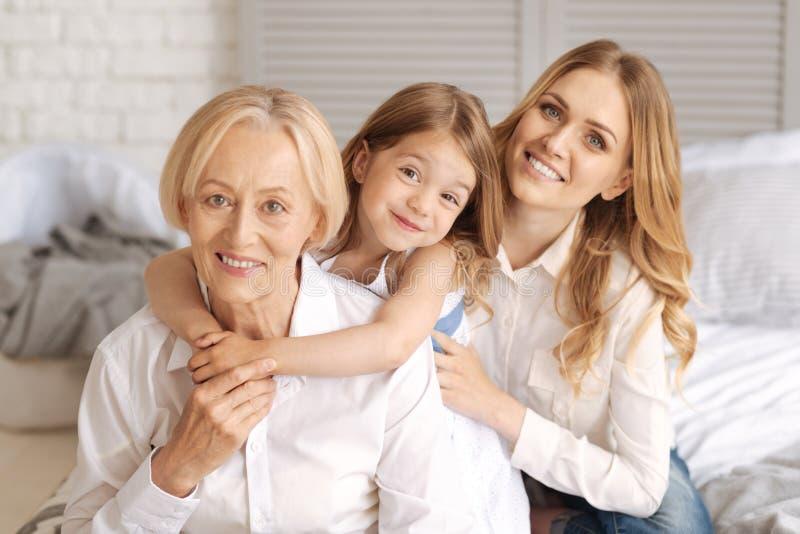 Trzy pokolenia kobiety siedzi za each inny zdjęcie stock