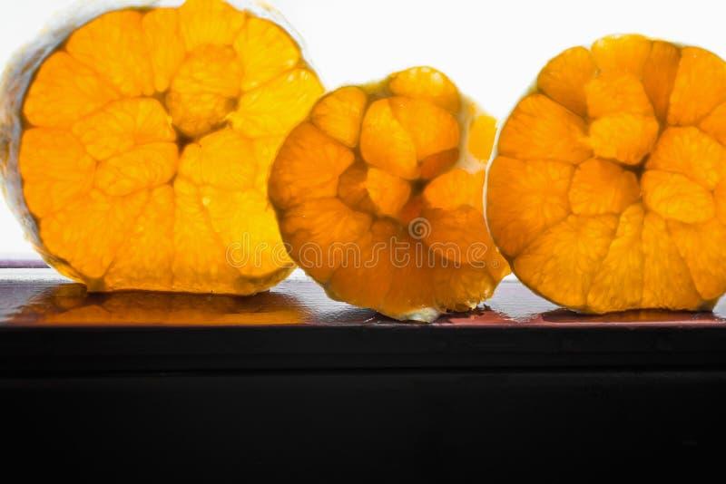 Trzy pomarańcze pokrajać na kołach z ładną strukturą inside obraz stock