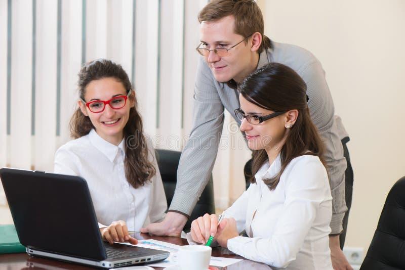 Trzy pomyślnego ludzie biznesu pracuje przy biurem obraz royalty free