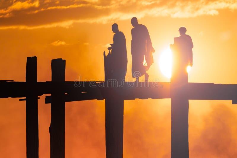 Trzy postaci krzyżuje most przy zmierzchem zdjęcie stock