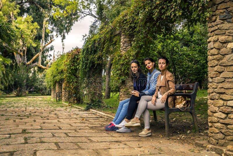 Trzy potomstwa i atrakcyjnych kobiety siedzi na ławce zdjęcia stock
