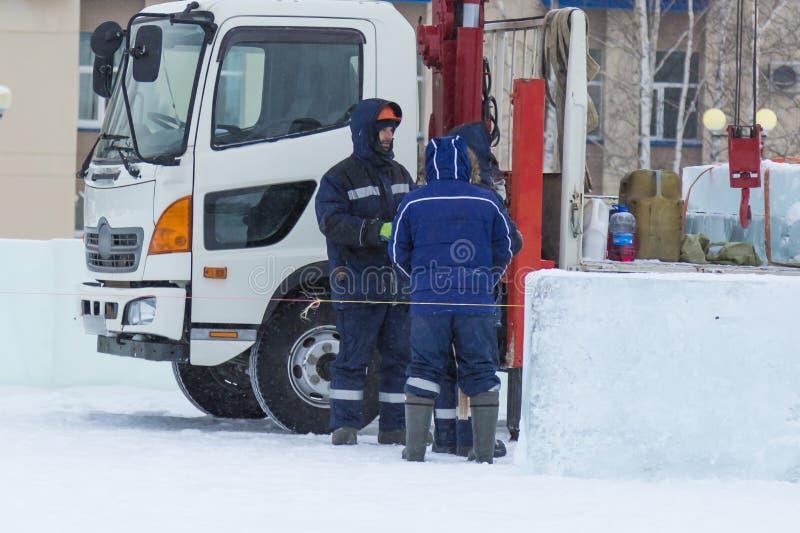 Trzy pracownika opowiadają hydraulicznego dźwignięcie zdjęcia royalty free