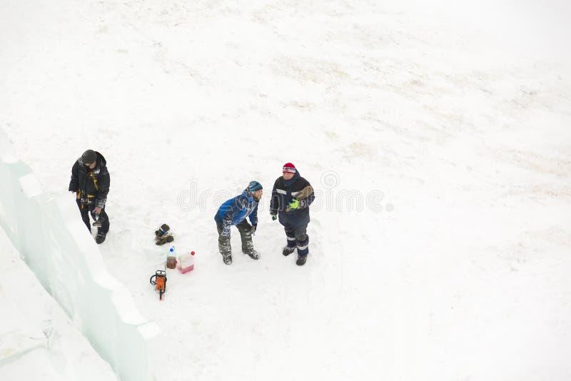 Trzy pracownika przy instalacją lodowy miasteczko zdjęcia stock