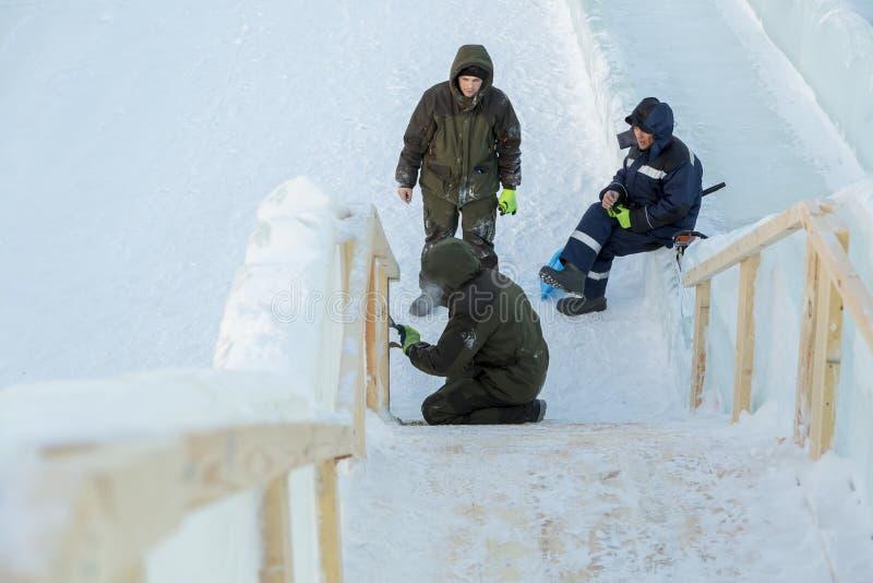 Trzy pracownika przy instalacją lodowy miasteczko obrazy royalty free