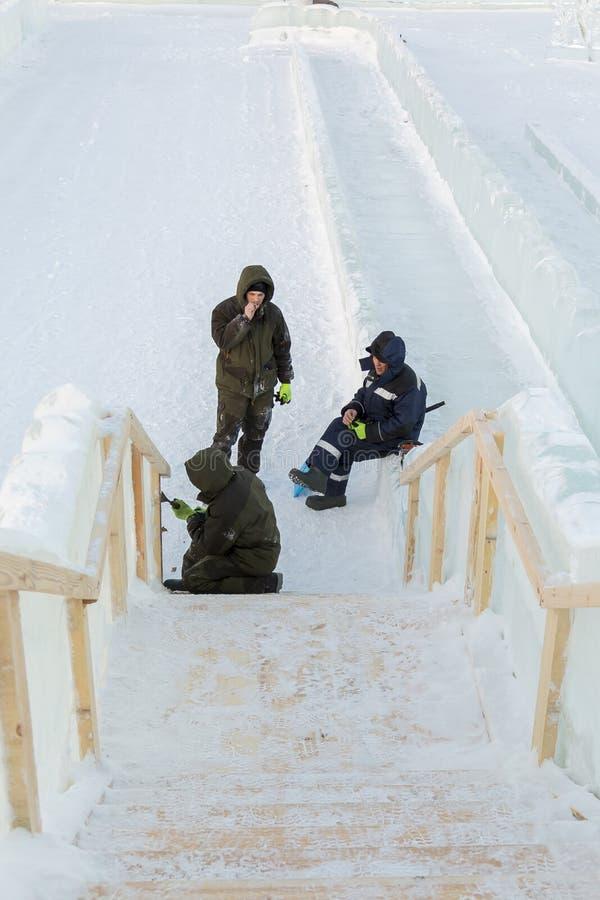 Trzy pracownika przy instalacją lodowy miasteczko obraz royalty free