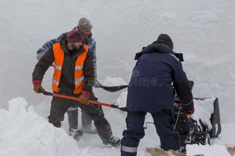 Trzy pracownika w śnieżycy podczas śnieżnego usunięcia zdjęcia royalty free