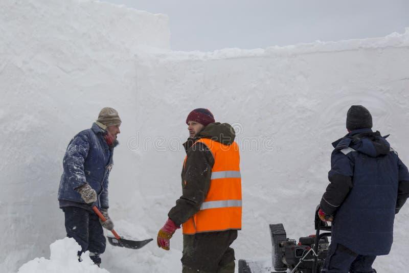 Trzy pracownika w śnieżycy podczas śnieżnego usunięcia zdjęcie stock