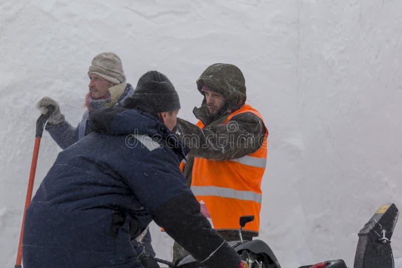 Trzy pracownika w śnieżycy podczas śnieżnego usunięcia fotografia stock