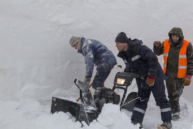 Trzy pracownika w śnieżycy podczas śnieżnego usunięcia fotografia royalty free