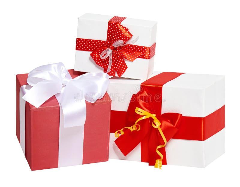 Trzy prezenta pudełka dekorujący faborek, jedwabniczy czerwony łęk i, przedmiot na białym pracownianym tle odizolowywającym obraz stock