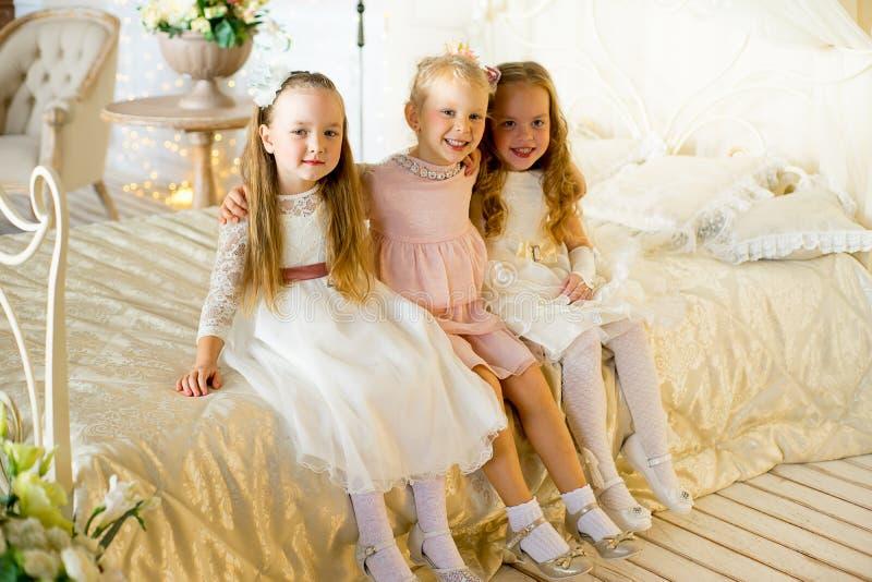 Trzy princess mały obsiadanie na łóżku obrazy stock
