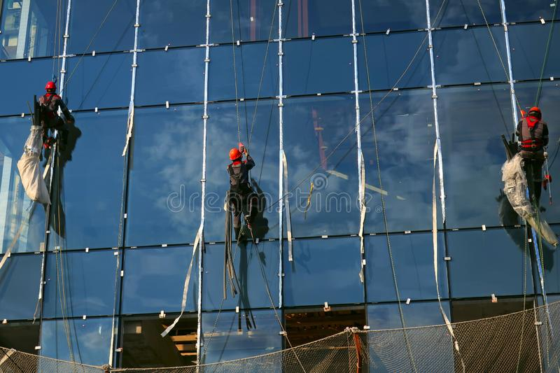 Trzy przemysłowego arywisty na szklanej fasadzie fotografia royalty free