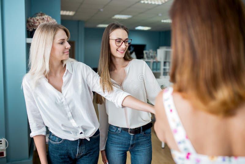 Trzy przyglądającej ładnej kobiety jest ubranym białe koszula są przyglądający krawczyna atrapa Moda, krawczyny warsztat fotografia stock