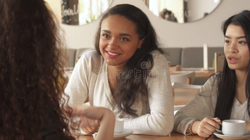 Trzy przyjaciół żeńska gadka przy kawiarnią zdjęcia stock