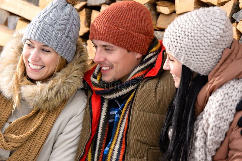 Trzy przyjaciela śmia się zimę plenerową odziewają fotografia stock