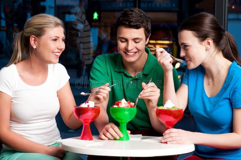 Trzy przyjaciela cieszy się kusicielskiego deser obraz stock