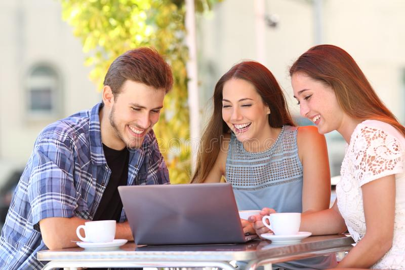 Trzy przyjaciela ogląda środek zawartość na laptopie w barze zdjęcie stock