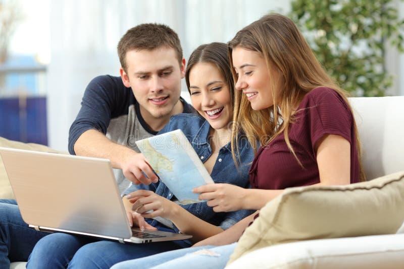Trzy przyjaciela planuje podróż w domu zdjęcie stock