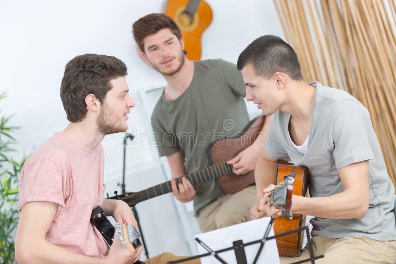 Trzy przyjaciela próbuje z gitarą zdjęcie royalty free