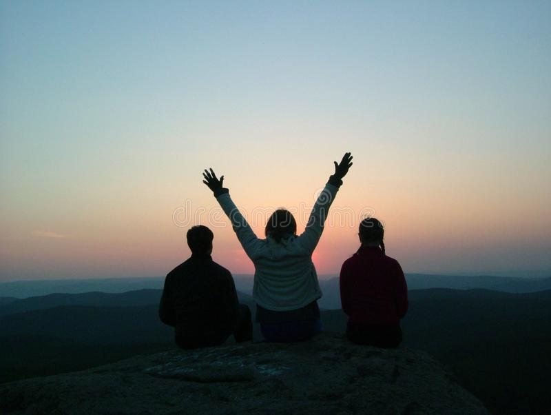 Trzy przyjaciela siedzą na górze góry i cieszą się zmierzch zdjęcia stock