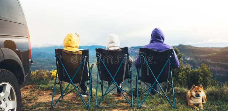 Trzy przyjaciela siedzą w campingów krzesłach na górze góry, podróżnicy cieszą się naturę i relaksują w odległość, turyści z psim obrazy royalty free