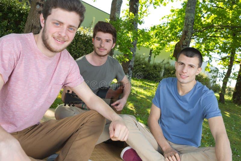 Trzy przyjaciela siedzi dalej w parku z gitarą obrazy stock