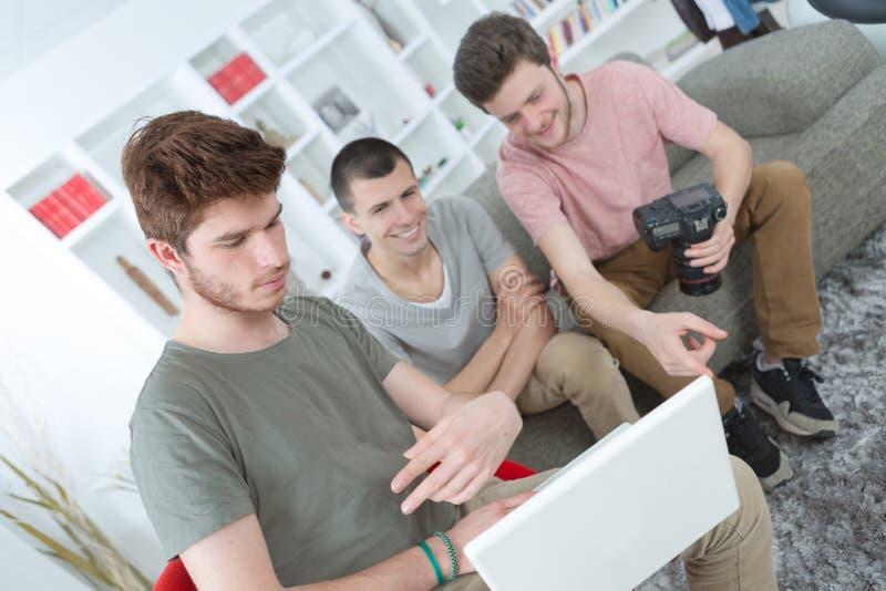 Trzy przyjaciela wpólnie przegląda fotografie ich strzelanina zdjęcie stock