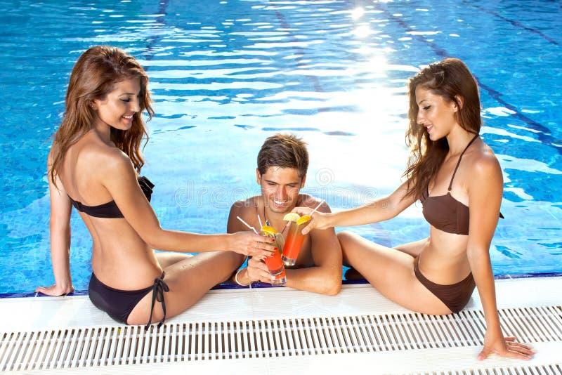 Trzy przyjaciela wznosi toast each inny przy basenem zdjęcie royalty free