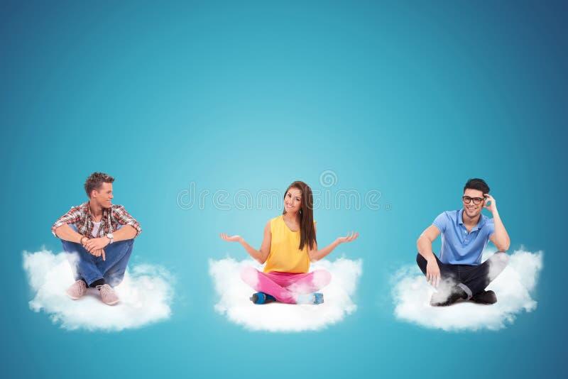 Trzy przypadkowego młodzi ludzie siedzi na chmurach obrazy stock