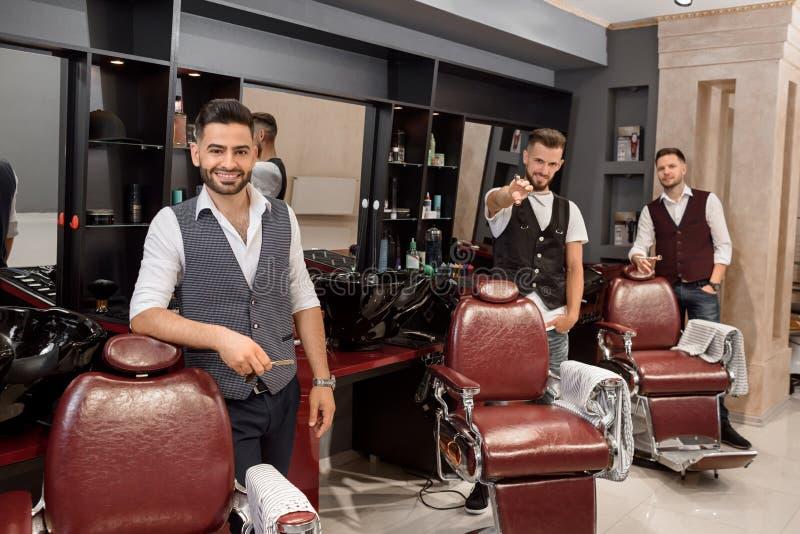 Trzy przystojnego fryzjera męskiego pozuje w zakładzie fryzjerskim blisko fryzjerów krzeseł zdjęcia stock