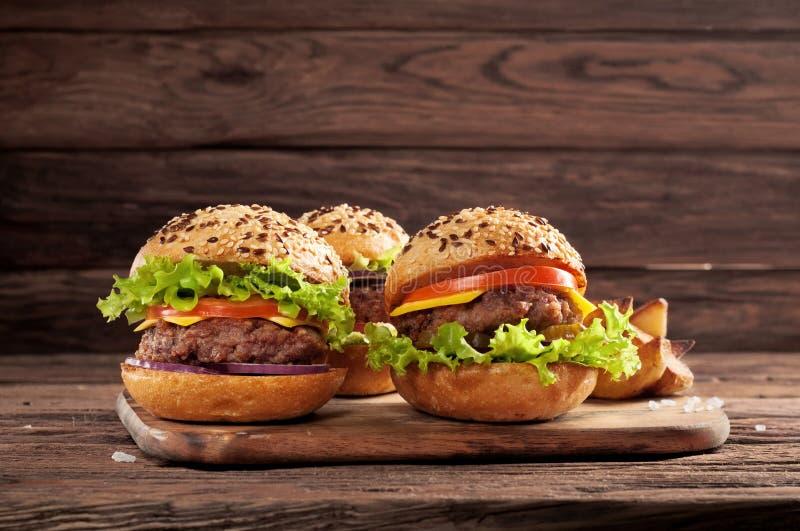 Trzy różnego hamburgeru na drewnianym tle zdjęcia stock