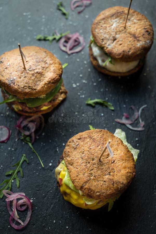 Trzy Różnego Smakowitego Dużego hamburgeru na zmroku kamienia tle, obraz stock