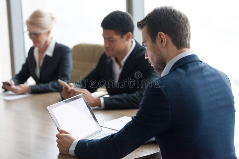 Trzy różnorodnego kolegi siedzi przy biurko pracą online wpólnie obrazy royalty free