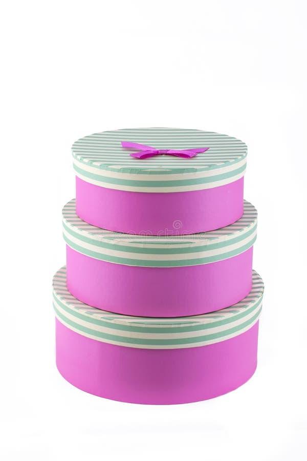 Trzy różowego cirkle prezenta pudełka z okręgiem paskowali pudełkowatą pokrywę z różowym faborkiem i łękiem zdjęcia royalty free