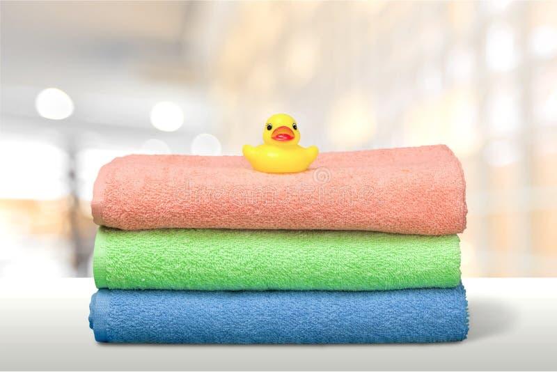 Trzy ręcznika i gumowej kaczka na łazience fotografia stock