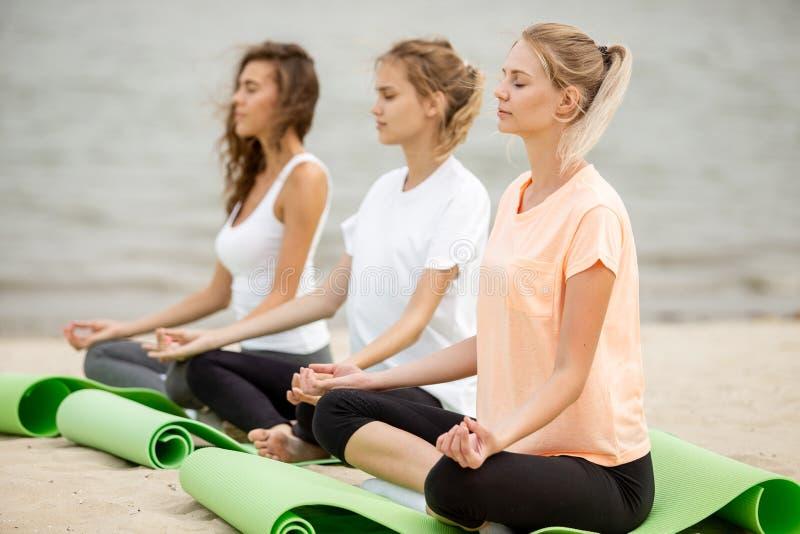 Trzy relaksuj?cej m?odej dziewczyny siedz? w lotosowych pozycjach z przymkni?? oczami robi joga na matach na piaskowatej pla?y na obraz royalty free