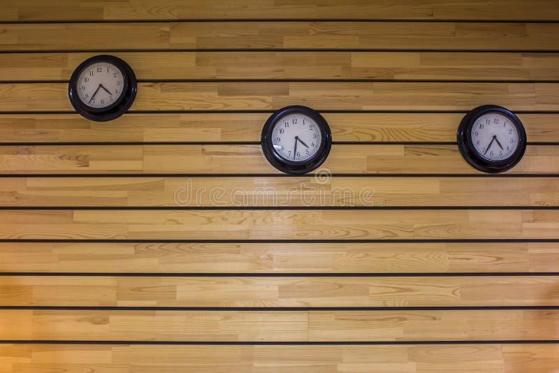 Trzy round czarnego zegaru na ścianie drewniany światło - szary kolor żółty wsiada Horyzontalne linie naturalna nawierzchniowa te obrazy royalty free