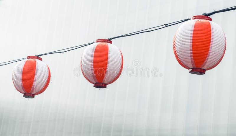 Trzy round japońskich lampionów Chochin papierowy biały obwieszenie na girlandy nieba tle obrazy stock