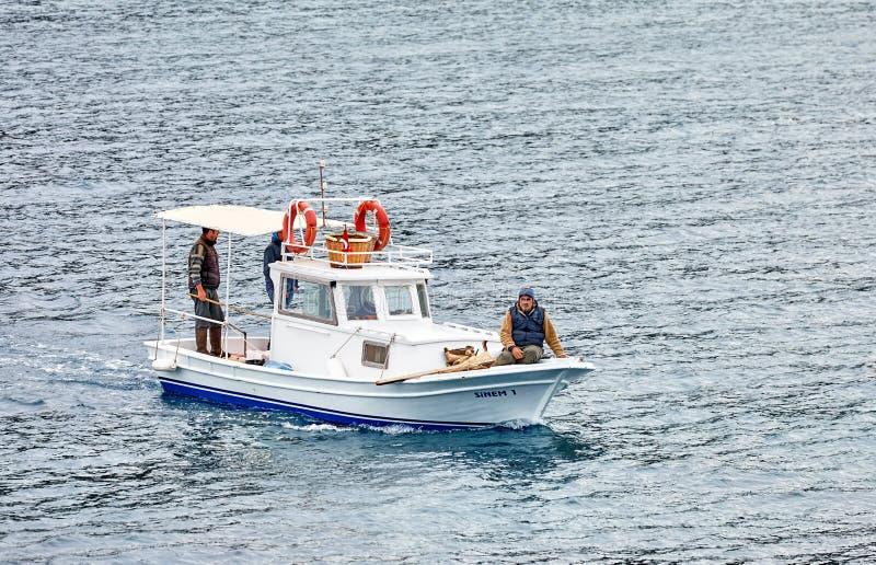 Trzy samiec Turecki rybak żegluje nad morzem w Gumusluk na białej tradycyjnej łodzi rybackiej, Bodrum, Turcja obrazy stock