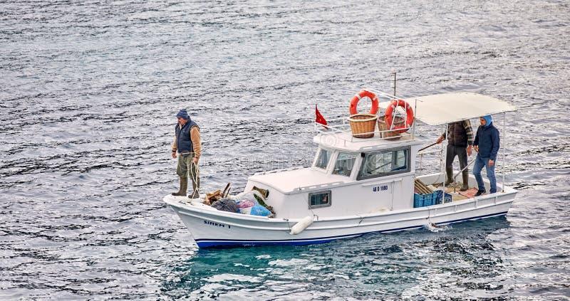 Trzy samiec Turecki rybak żegluje nad morzem w Gumusluk na białej tradycyjnej łodzi rybackiej, Bodrum, Turcja fotografia stock
