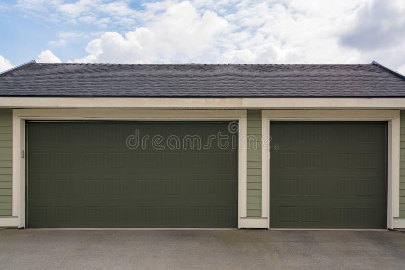 Trzy samochodowy garaż z szerokim drzwi na chmurnego nieba tle fotografia stock