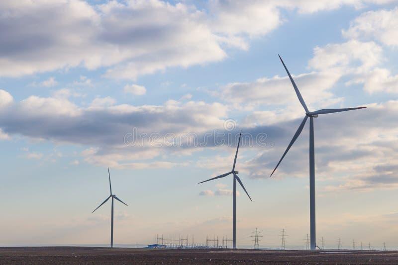 Trzy silnik wiatrowy na rolniczej ziemi z chmurnym niebem w tle zdjęcia stock