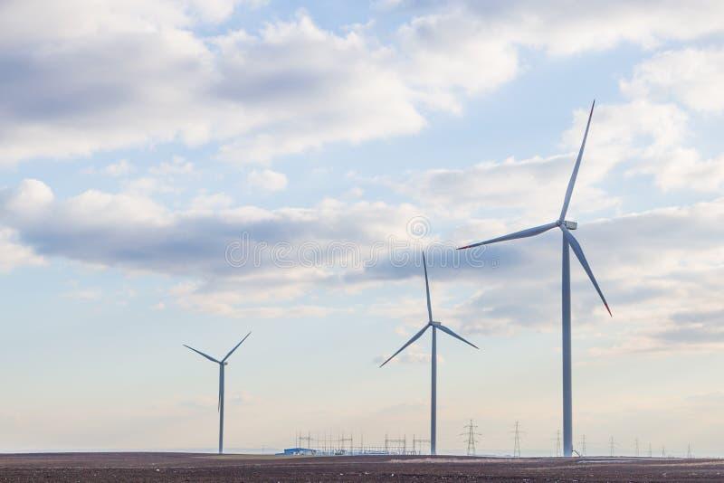 Trzy silnik wiatrowy na rolniczej ziemi z chmurnym niebem w tle obrazy royalty free