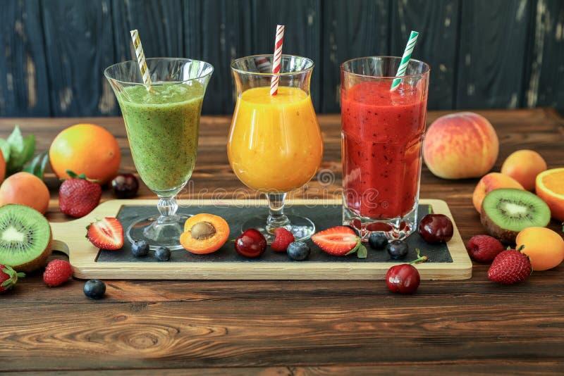 Trzy smoothies od różnych owoc i jagod tak jak kiwi, pomarańcze, brzoskwinia, morela, wiśnia, truskawka, malinka zdjęcia royalty free