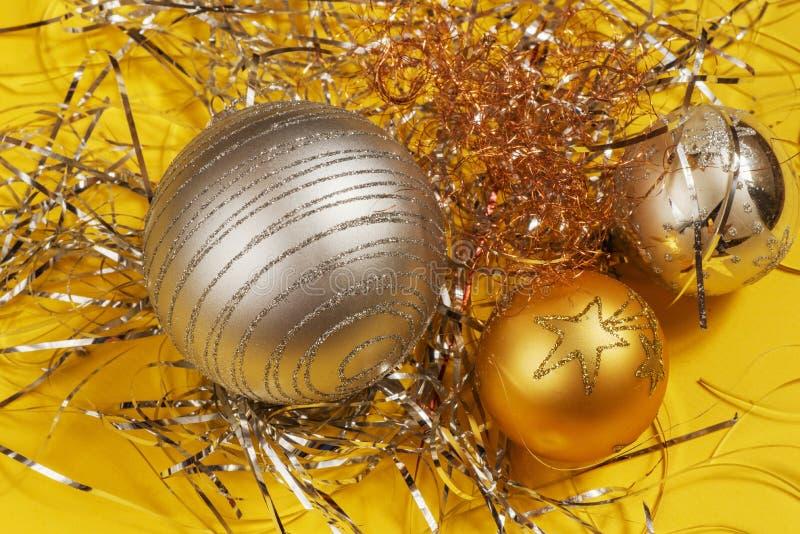 Trzy srebny i złoci dekoracyjni boże narodzenia balowi na kruszcowej nici na żółtym tle zdjęcia royalty free