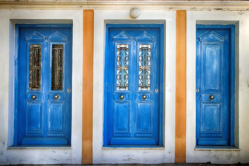 Trzy starego błękitnego drzwi, Simi Grecja fotografia stock