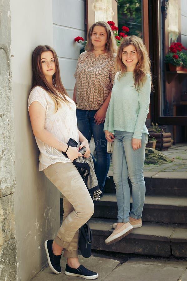 Trzy stylowe wesołe hipsterki kobiece modne ubrania pozujące się na ulicy europe City, radosne chwile koncepcja przyjaźni obraz royalty free