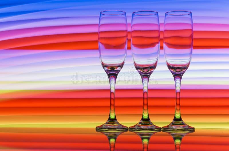 Trzy szampańskiego szkła z tęczą kolorowy lekki obraz za one z rzędu obraz stock